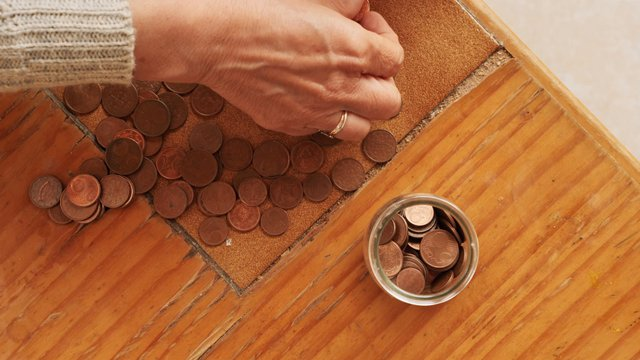 Woman Throws Coins In The Jar Top View thumbnail