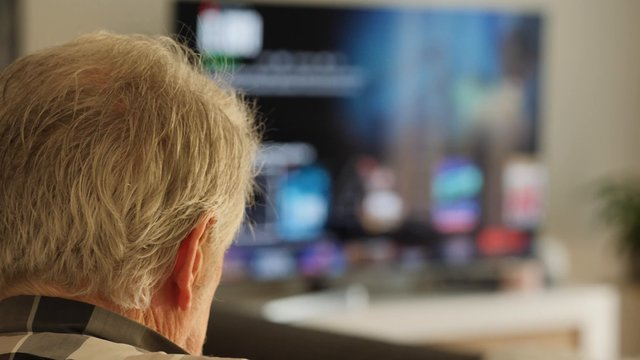 Old Man In Living Room With Netflix On TV thumbnail