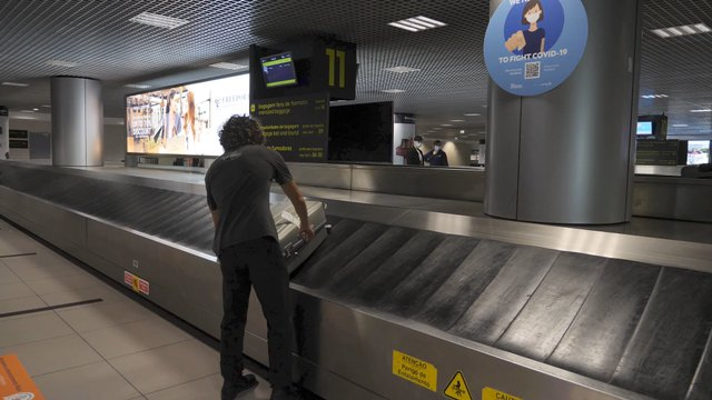 Guy Picks up a Suitcase From the Luggage Carousel thumbnail