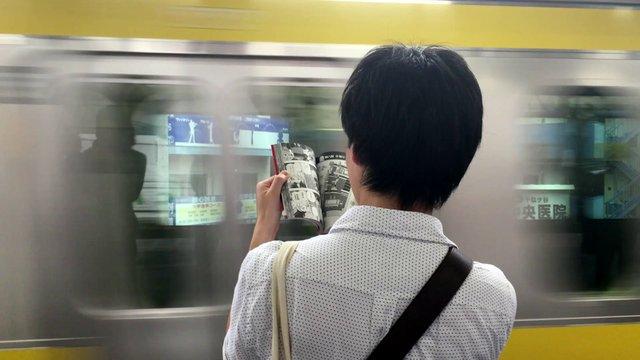Man Reading Comics in Subway Station thumbnail