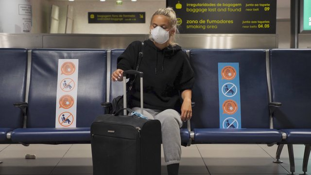 Blonde Girl Pulls Her Suitcase in an Empty Airport thumbnail