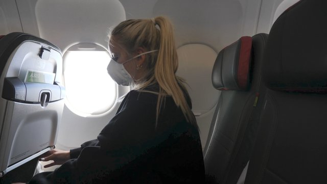 A Girl Takes Her Laptop and Starts Working in a Plane thumbnail