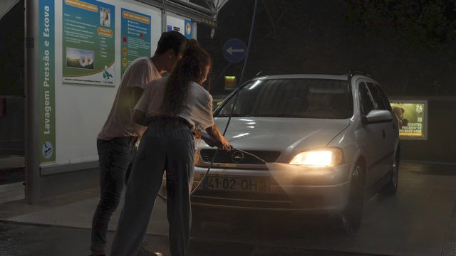 Girl and Guy Together Spray a Car With a Jet of Water thumbnail