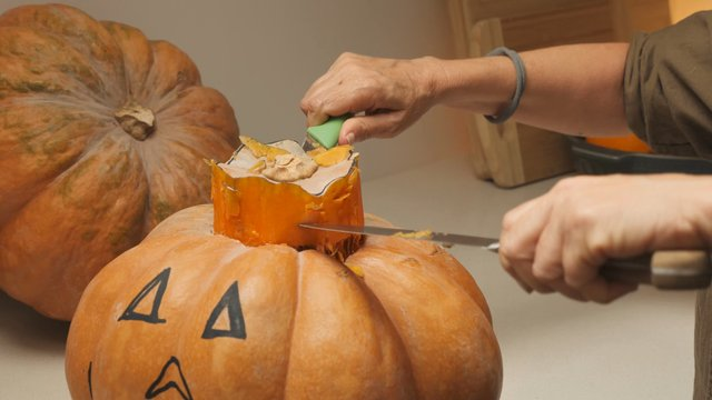 A Woman Pulls Out the Middle of a Pumpkin thumbnail