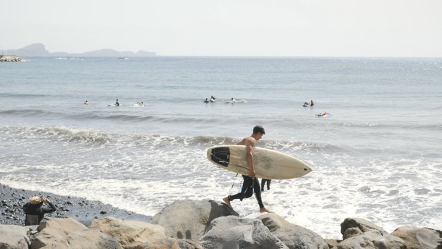 A Guy Goes on the Stones With a Surfboard thumbnail