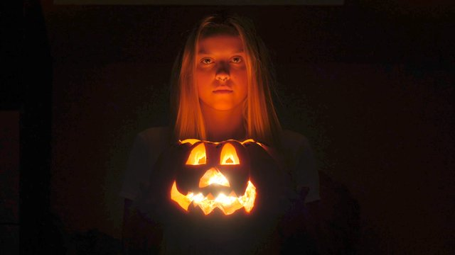 A Blonde Girl Holds Jack O' Lantern thumbnail