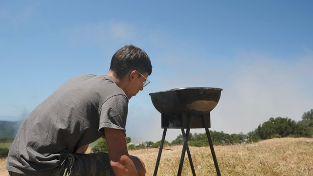 Young Man Inflates the Fire in the Grill thumbnail