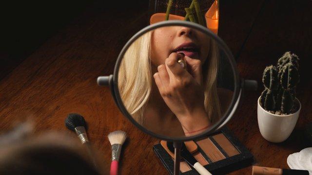Blonde Girl Applying Pink Lipstick  thumbnail