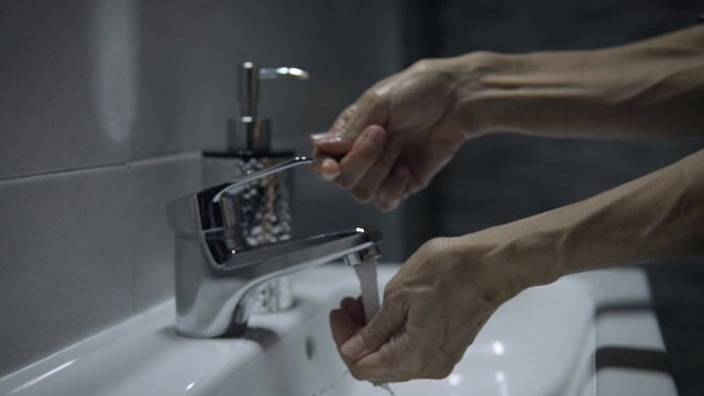 Lady Washing Her Hands In Sink thumbnail