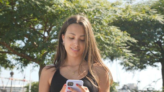 Brunette Girl Texting in the Park  thumbnail