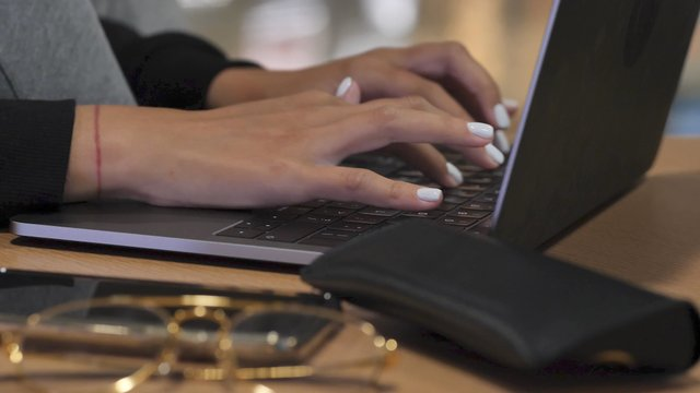 Female Hands Type on a Laptop Keyboard thumbnail