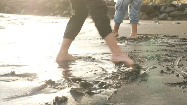 A Couple Play by Legs With Wet Sand thumbnail