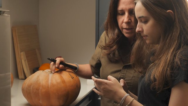 Mom and Daughter Discuss a Halloween Decoration thumbnail