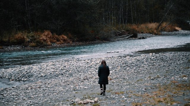 Woman Strolls Near a River   thumbnail