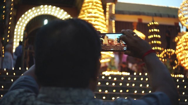 Man Taking Photo Of Temple Festival Lights thumbnail