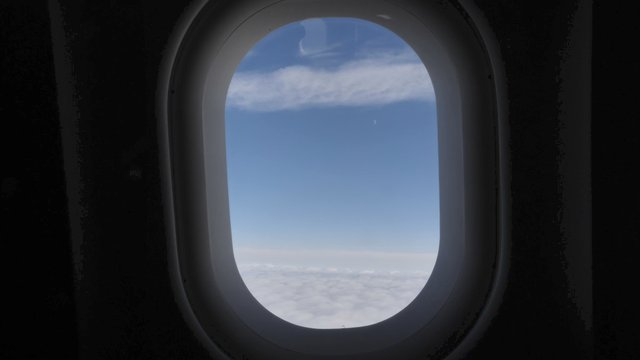 View From Airplane Porthole to the Blue Sky and Clouds thumbnail