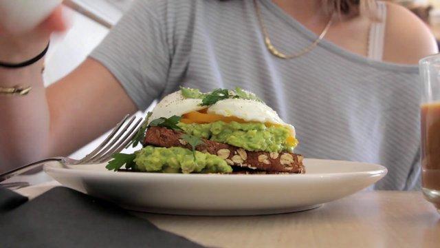Woman Eating Avocado & Egg Sandwich thumbnail