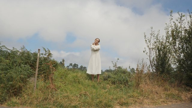Girl in a White Dress Stands in the Field thumbnail