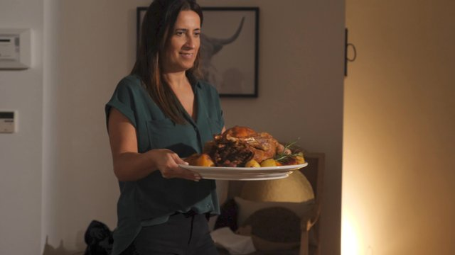 A Woman Puts Roasted Turkey on a Dining Table thumbnail