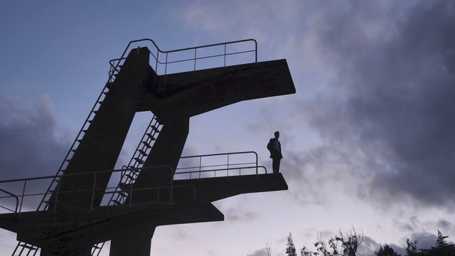 A Man Stands on the Edge of the High Springboard and Looks Around thumbnail