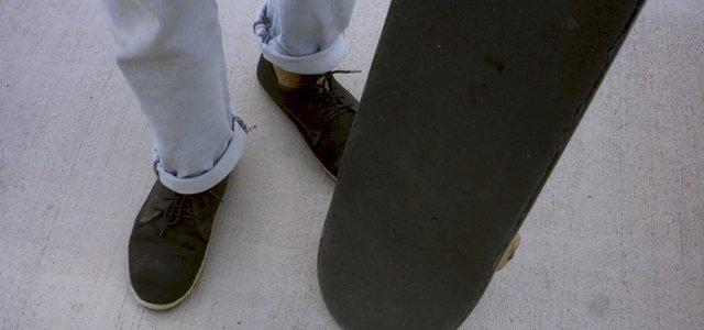 Man Twists a Skateboard on the Asphalt thumbnail