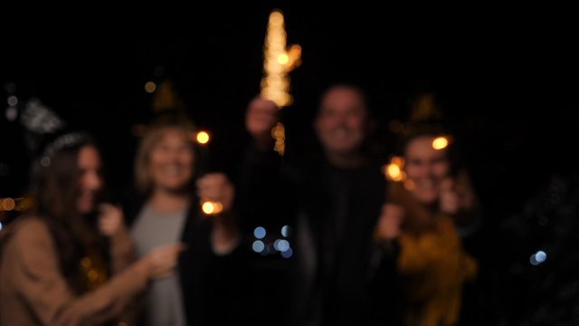 A Smiling Family Waves Sparklers thumbnail