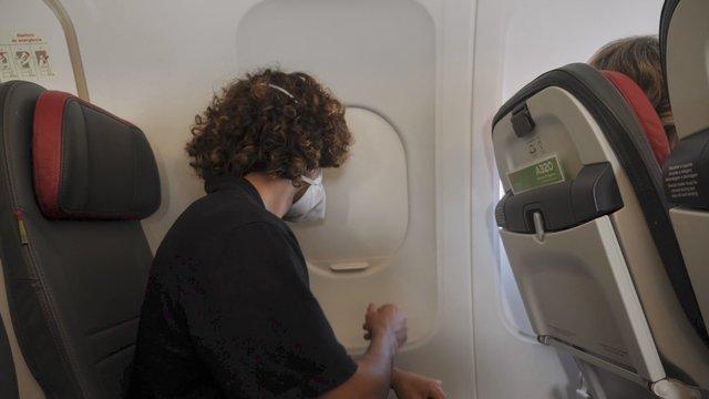 Close-up Shot of Male Passenger Opens Airplane Window thumbnail