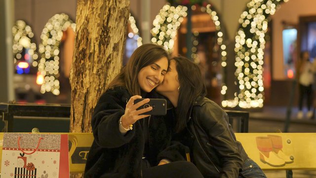 Girlfriends Make Selfie in an Illuminated Square thumbnail