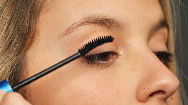 Girl Applying Mascara On Eyelashes thumbnail