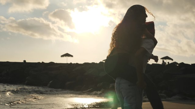 A Guy Spins a Girl on His Back Against a Sunset Background thumbnail