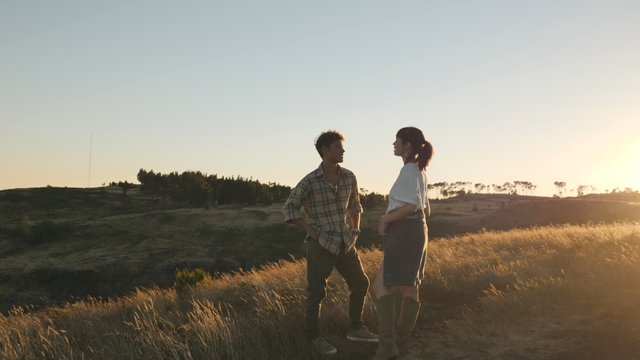 A Couple Stands in a Field and Talks thumbnail