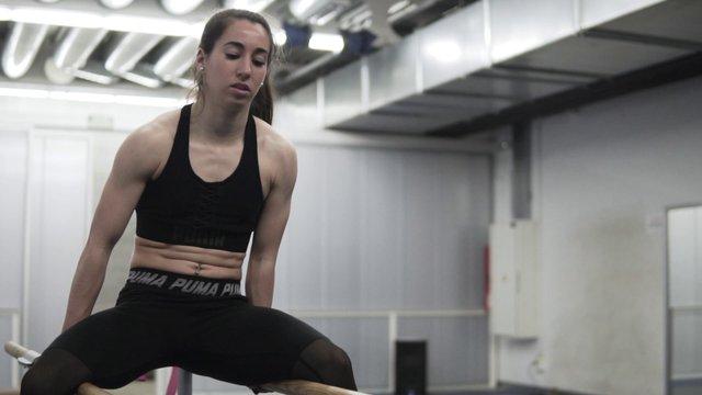 Woman Doing Tricks On Gymnastic Bars thumbnail
