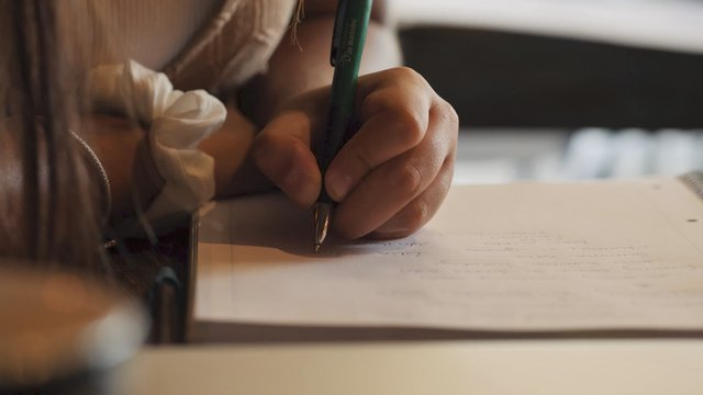 Student Writing Notes in a Notebook thumbnail