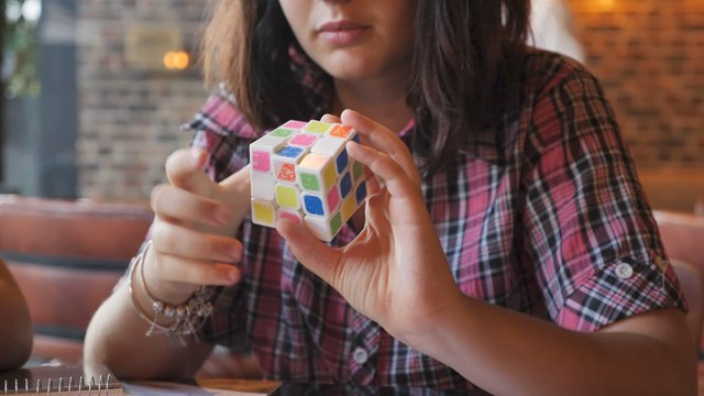 Girl Playing with a Rubik's Cube thumbnail